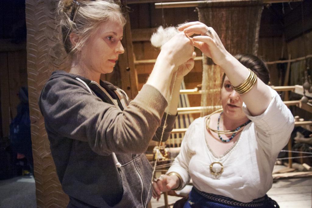 two women making wool thread